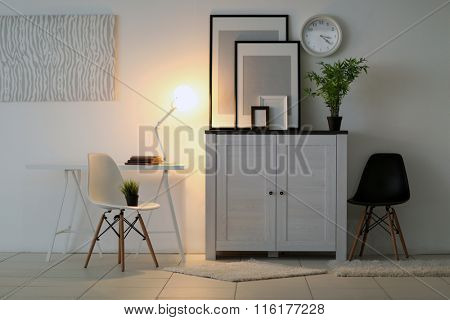 Room interior with commode with chairs, plant, frames and clock on white wall background