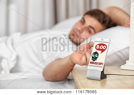 Beautiful young man waking up with mobile alarm clock