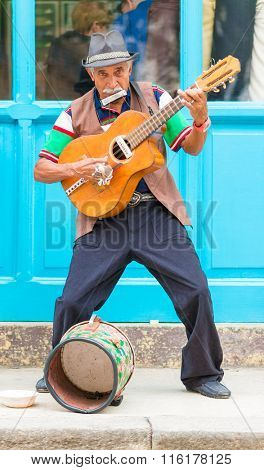 HAVANA,CUBA - JANUARY 26,2016 : Senior guitarist playing traditional cuban music on a street in Old Havana