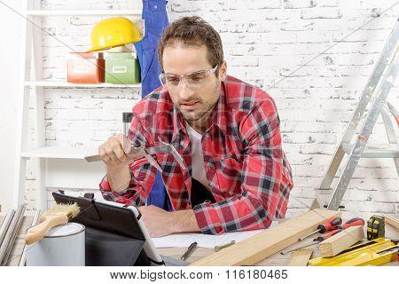 Young Carpenter Using Caliper, In His Workshop