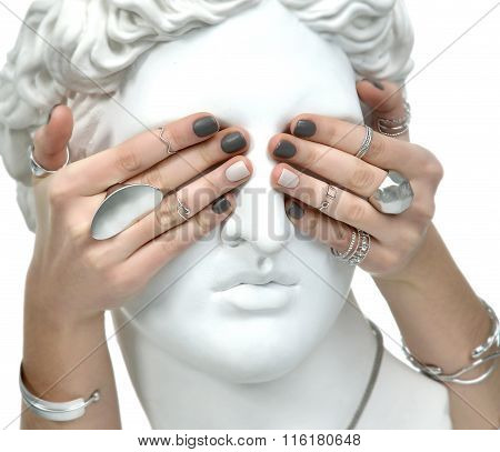 Beautiful Manicure Woman Hands Covering The Eyes Of An Apollo Statue