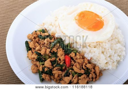 Rice topped with stir-fried chicken, basil and fried egg on white background