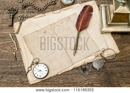 Antique office supplies and accessories on wooden table. Vintage used paper feather pen. Nostalgic sentimental background
