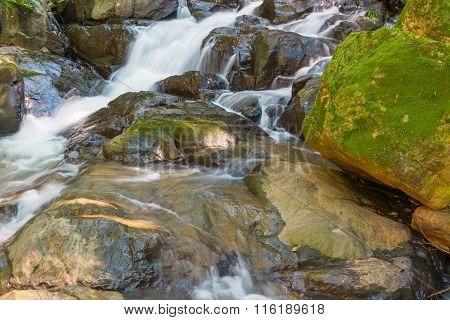 Water Falls Over A Jumble Of Moss-covered Boulders In Forest.