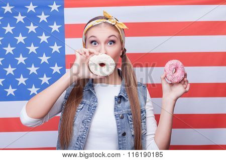 Cheerful young girl is eating American food