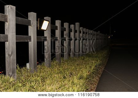 Wooden Fence Against Lamp In Night.