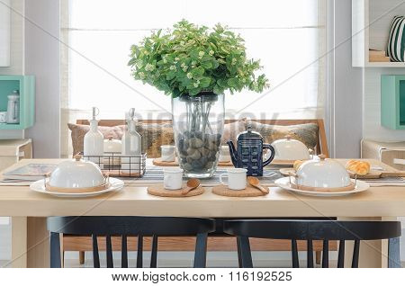Glass Vase Of Plant On Wooden Dinning Table With Black Chair