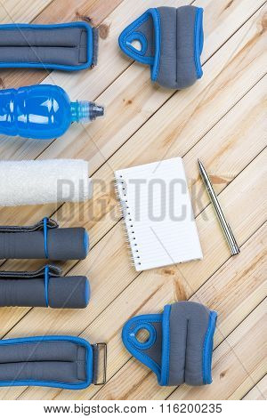 Dumbbells, Weights, Towel, Drink, Notebook.