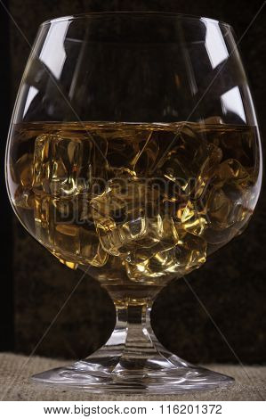 glass of cognac with ice closeup background