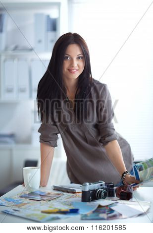 Young woman photographer processing pictures sitting on the desk