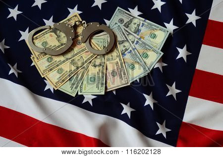 handcuffs on money background and american flag
