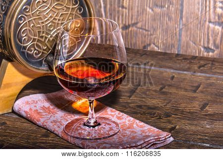 Barrel With A Glass Of Cognac On The Old Table
