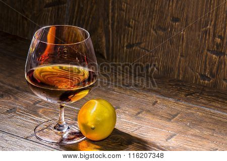 Brandy Shimmers With Rich Colors In A Goblet On Old Table