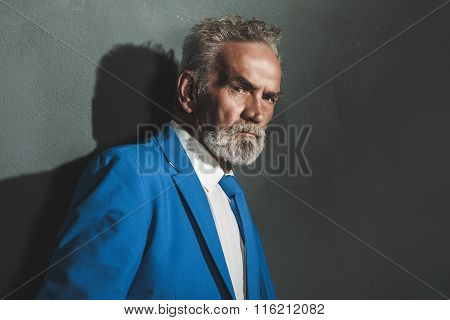 Thoughtful Elegant Old Man Leaning Against Wall