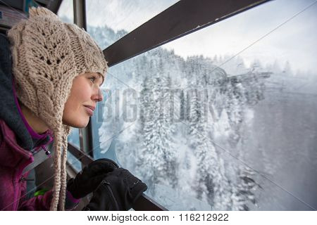 Pretty, young woman admiring splendid winter scenery from a cablecar cabin in high mountains (shallow DOF; color toned image)