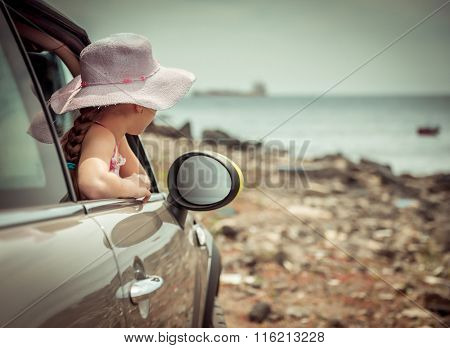 little girl traveling by car at sea back view