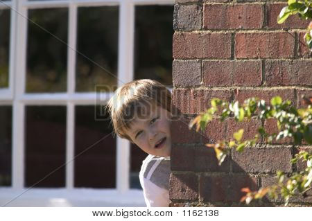 Boy Peeking Round A Wall
