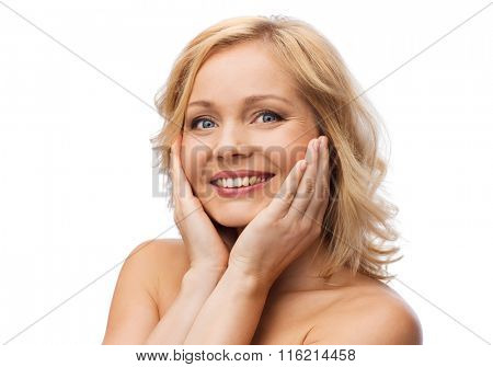 smiling woman with bare shoulders touching face