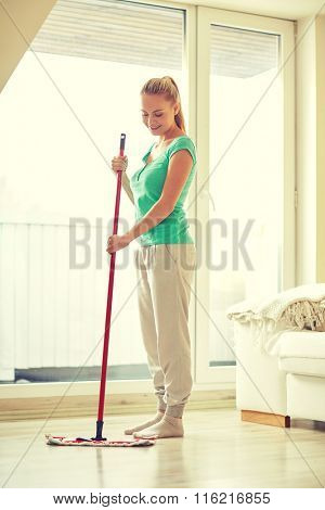 happy woman with mop cleaning floor at home
