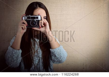 Portrait of pretty young woman taking photo with retro noname soviet photo camera. Photographer getting pictures in hipster style indoor over canvas background. Image toned.