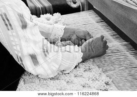 Elderly Woman In Lace Shirt Weaving On A Loom