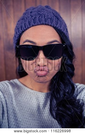 Asian woman pouting against wooden wall