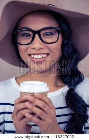 Attractive Asian woman with hat holding disposable cup looking at the camera