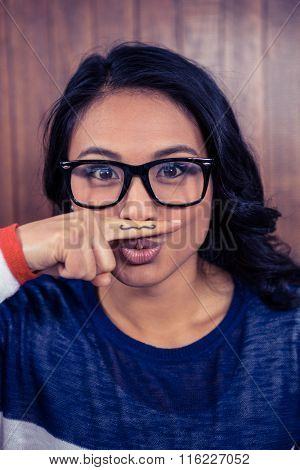 Asian woman with mustache on finger against wooden wall