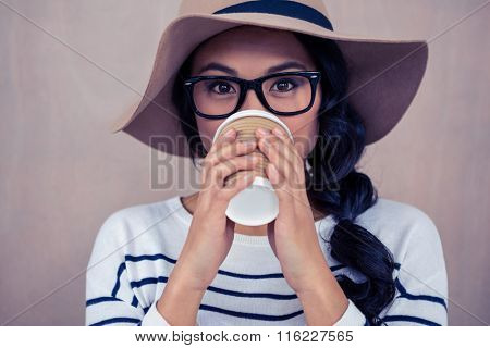 Attractive Asian woman drinking by disposable cup and looking at the camera