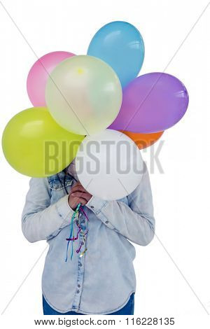 Asian woman hiding her face behind colorful balloons on white screen