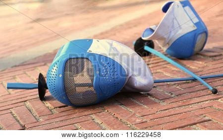 Equipment Fencing Mask And Foil Resting On The Ground After The Defeat