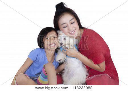 Cute Girl And Her Mother Hug Maltese Dog