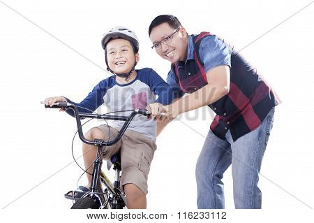 Dad Helps His Child To Ride A Bicycle