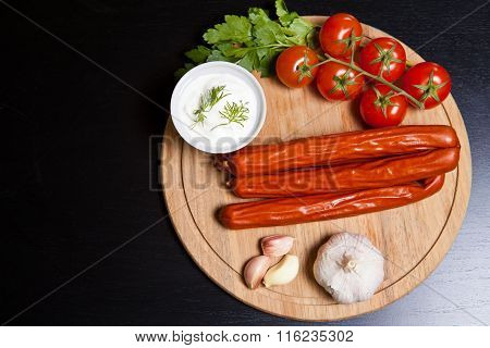 Hunting Sausages With Vegetables And Sauce On A Cutting Board On A Dark Background