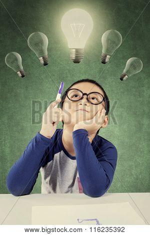 Smart Little Boy Holding A Pen Under Light Bulb