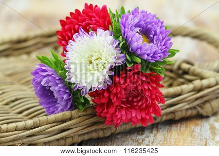 Colorful aster flower bouquet on wicker tray with copy space