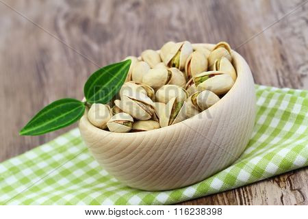 Pistachio nuts in wooden bowl on checkered cloth with copy space