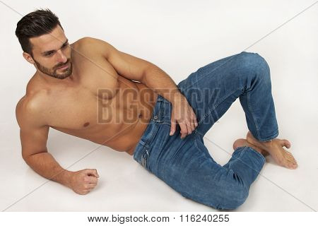 Hansome Modern Strong Muscular Man In Blue Jeans Laying On White Background In Studio, With Beard