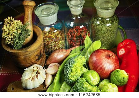 Glass bottles with spices, fresh vegetables, wooden mortar