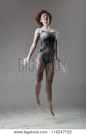 Beautiful expressive ballet dancer jumping with flour at studio