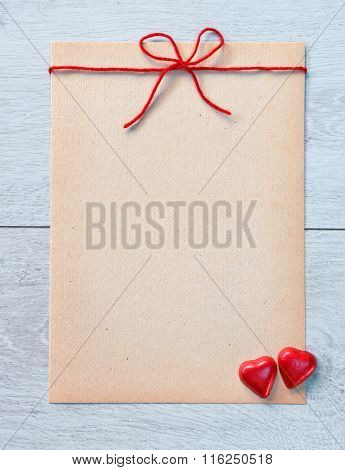 Vintage Letter and two hearts candies on a white wooden background