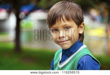 Closeup portrait of beautiful little boy on background summer park