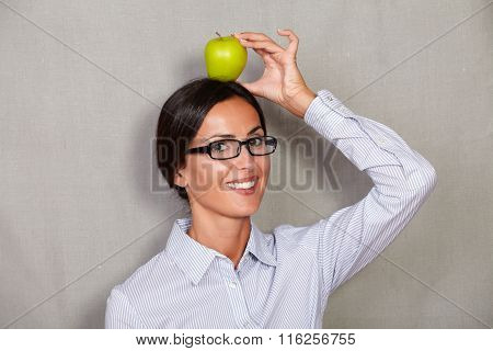 Smiling Brunette Lady Holding Apple On Head