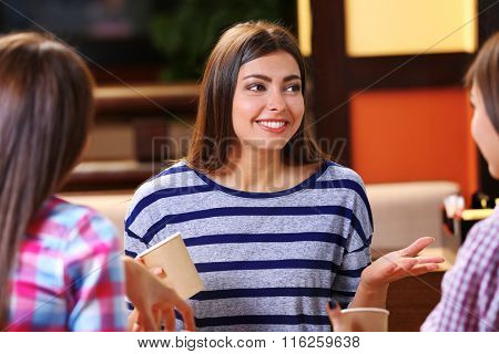 Beautiful girls speaking in cafe