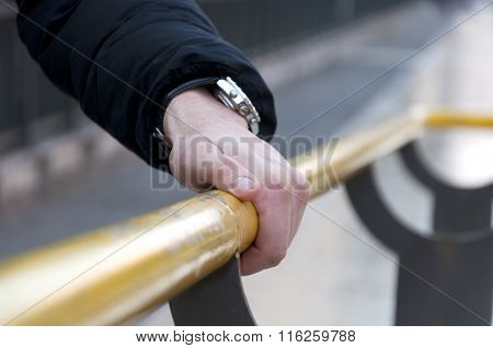 male hand holding on to the handrail