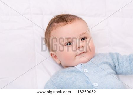 Cute infant boy lying in bed.