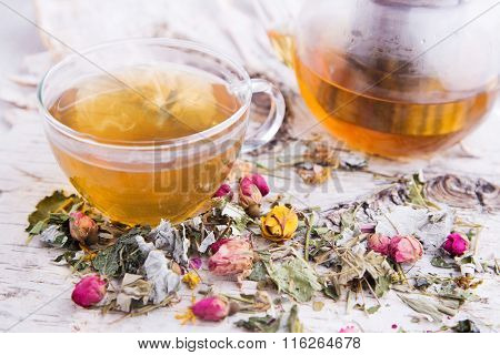 Clear hot cup of roses herbal tea with teapot