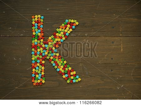 Letter K from alphabet made with star shape candy on a wooden background
