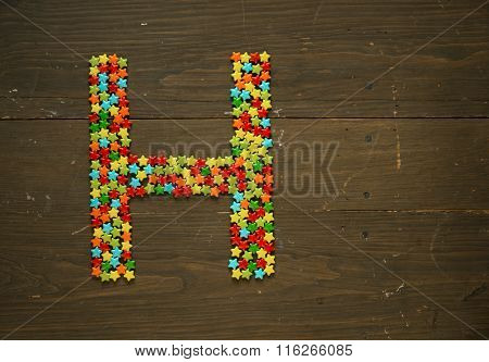 Letter H from alphabet made with star shape candy on a wooden background