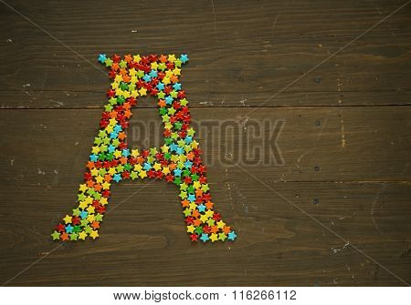 Letter A from alphabet made with star shape candy on a wooden background